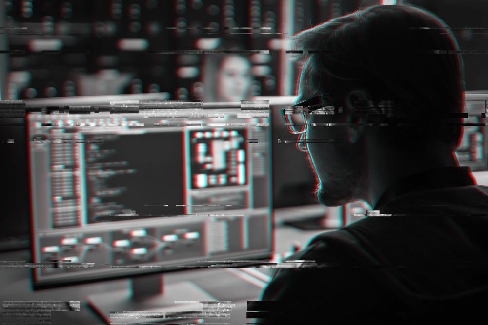Ein Mann sitzt am Schreibtisch mit drei Bildschirmen.