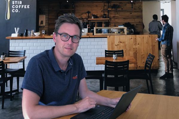 Steffen Landsberg mit einem Laptop im Café